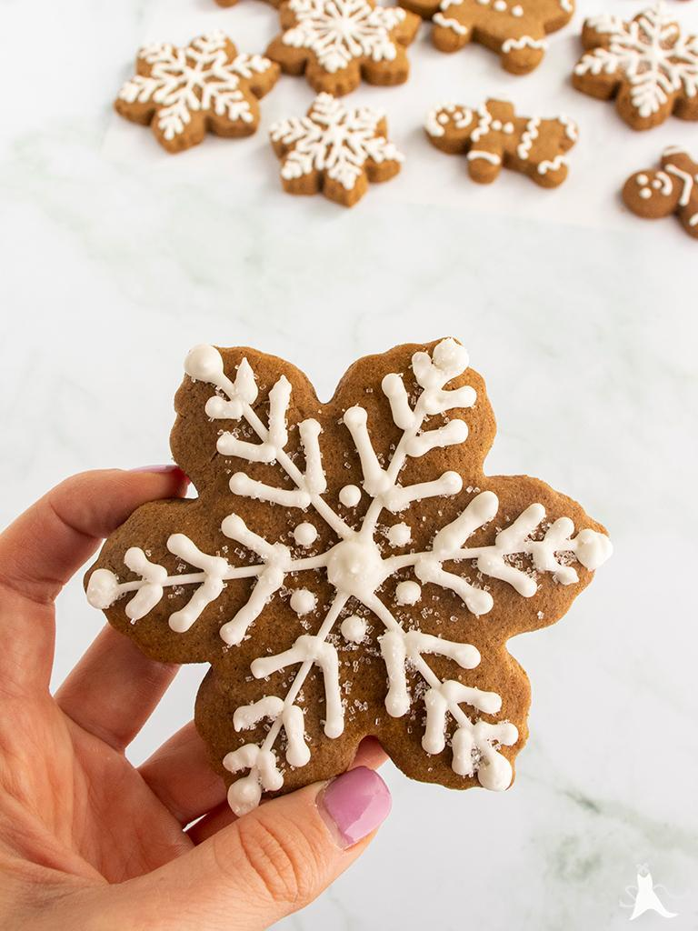Hand holding a snowflake-shaped gingerbread cookie decorated with royal icing and sprinkles