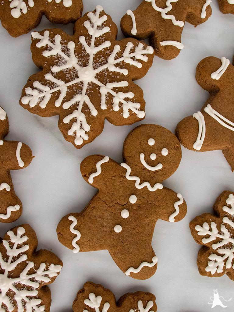 Gingerbread men and snowflake-shaped cookies decorated with royal icing and clear sprinkles