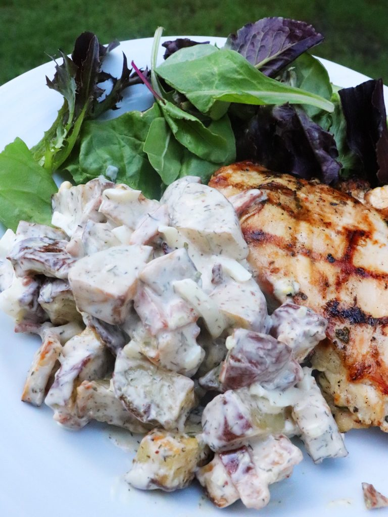 potato salad served with herb grilled chicken and spring mix salad