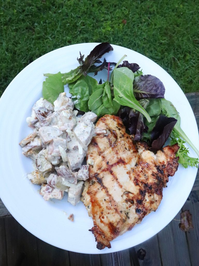 Overhead view of potato salad with grilled chicken and spring mix salad